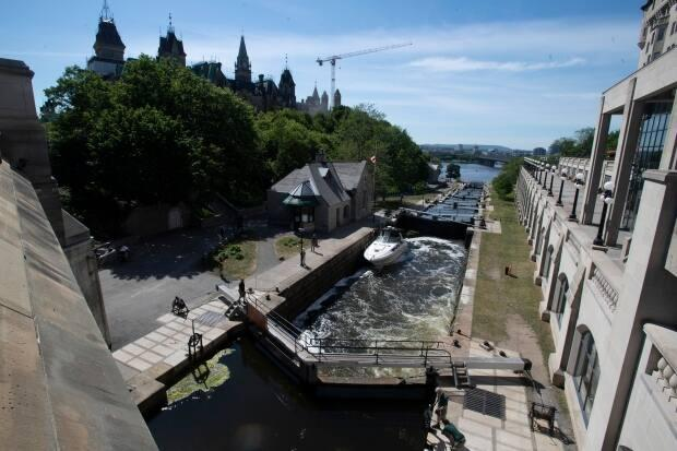 A boat waits for the water to rise in the Ottawa Locks on May 31, 2021. The pandemic delayed the start of the 2021 boating season on the Rideau Canal. (Adrian Wyld/Canadian Press - image credit)