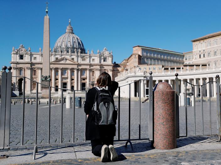 A woman prays on her knees in front of an empty St. Peter's Square as Pope Francis gives his weekly general audience via transmitted video a day after the Vatican closed the square and Basilica due to coronavirus concerns, as seen from Rome, Italy March 11, 2020. REUTERS/Guglielmo Mangiapane