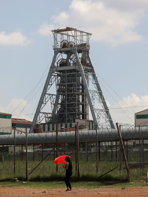 FILE PHOTO: A woman walks past a shaft at Harmony Gold's Doornkop mine, 30km west of Johannesburg