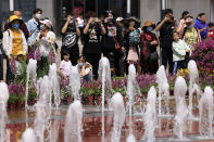 Residents watch a fountain show along the Wangfujing shopping district in Beijing Tuesday, May 11, 2021. The number of working-age people in China fell over the past decade as its aging population barely grew, a census showed Tuesday, adding to economic challenges for Chinese leaders who have ambitious strategic goals. (AP Photo/Ng Han Guan)