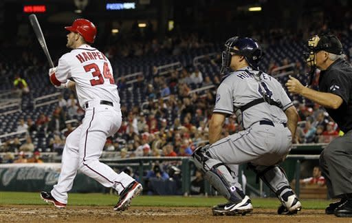 Washington Nationals' Bryce Harper (34), left, San Diego Padres catcher Nick Hundley, center, and home plate umpire Larry Vanover watch Harper's his first major-league home run during the third inning of baseball game, Monday, May 14, 2012, in Washington. (AP Photo/Haraz N. Ghanbari)