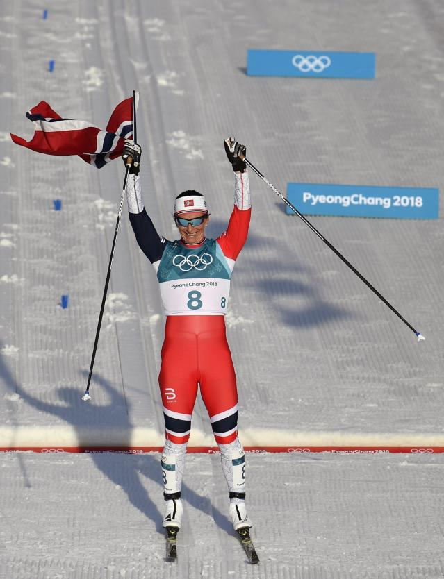 Cross-Country Skiing - Pyeongchang 2018 Winter Olympics - Women's 30km Mass Start Classic - Alpensia Cross-Country Skiing Centre - Pyeongchang, South Korea - February 25, 2018 - Gold medallist Marit Bjoergen of Norway celebrates victory while holding her national flag. REUTERS/Toby Melville