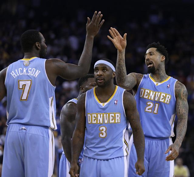 From left, Denver Nuggets' J.J. Hickson, Ty Lawson, and Wilson Chandler (21) celebrate during a time out against the Golden State Warriors during the second half of an NBA basketball game on Wednesday, Jan. 15, 2014, in Oakland, Calif. (AP Photo/Ben Margot)