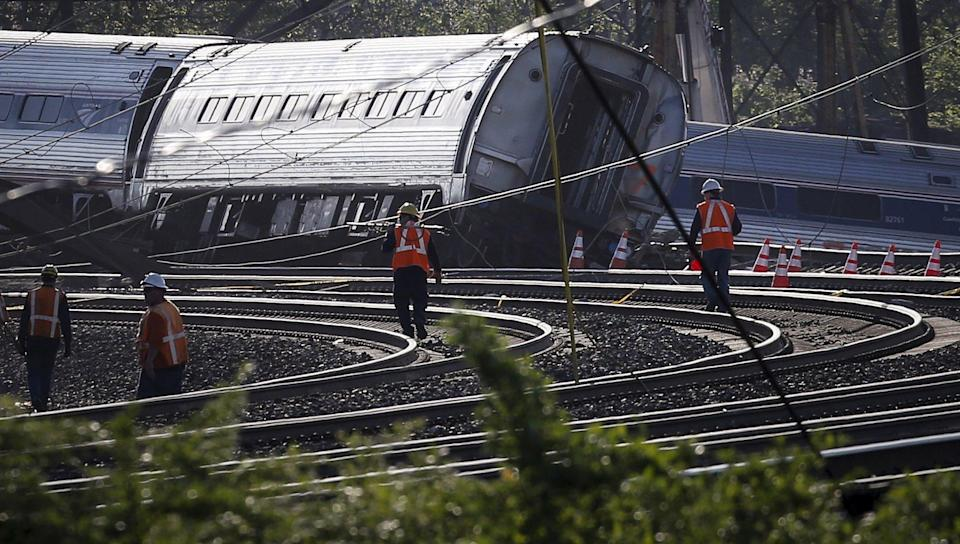 Men walk towards the site of a derailed Amtrak train in Philadelphia, Pennsylvania May 13, 2015. An Amtrak passenger train with more than 200 passengers on board derailed in north Philadelphia on Tuesday night, killing at least five people and injuring scores of others, several of them critically, authorities said. Authorities said they had no idea what caused the train wreck at about 9:30 p.m. local time that left some rail cars mangled, ripped open and strewn upside down and on their sides in the city's Port Richmond neighborhood along the Delaware River. REUTERS/Mike Segar TPX IMAGES OF THE DAY