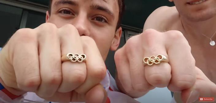 Tom Daley and Matty Lee show off their matching Olympic golden ring jewellery after they won gold medals in diving on Monday.