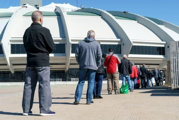 People wait in line at a COVID-19 vaccination clinic to receive the AstraZeneca vaccine at the Olympic Stadium in Montreal. Quebecers aged 45 and over can get the shot via appointment or walk-in sites starting tomorrow.