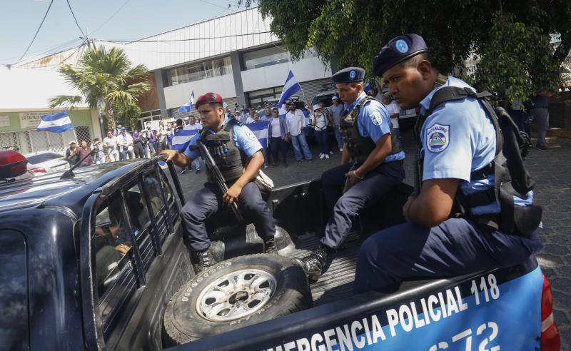 Police patrol near anti-government protesters wanting to march in Managua, Nicaragua, Wednesday, April 17, 2019. Police prevented the march to commemorate a year since Nicaraguan protesters took to the streets to oppose the government of President Daniel Ortega. (AP Photo/Alfredo Zuniga)