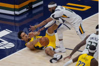Indiana Pacers guard Malcolm Brogdon (7) and Utah Jazz guard Mike Conley, right, battle for a loose ball in the first half during an NBA basketball game Friday, April 16, 2021, in Salt Lake City. (AP Photo/Rick Bowmer)