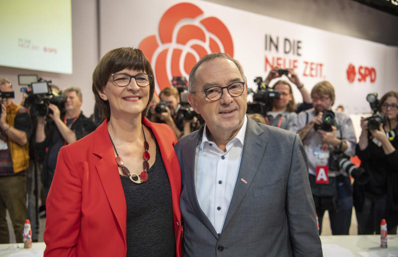Norbert Walter-Borjans stands alongside Saskia Esken, from right, at the beginning of the German Social Democrats, SPD, federal party conference in Berlin, Germany, Friday, Dec. 6, 2019. Members of the center-left party have choosen the left-leaning duo Norbert Walter-Borjans and Saskia Esken as their new leaders. This has to be confirmed by the delegates at the party meeting. (Bernd von Jutrczenka/dpa via AP)