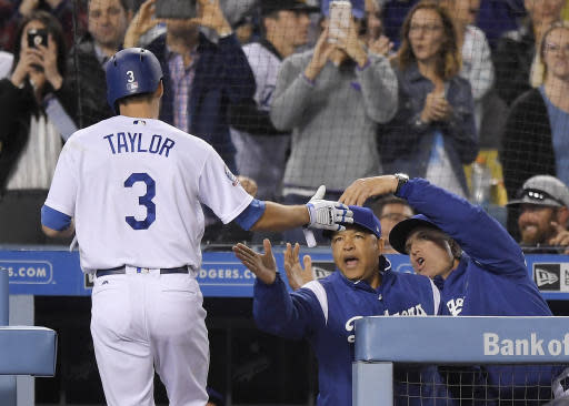 Los Angeles Dodgers' Chris Taylor, left, is congratulated by manager Dave Roberts, center, and coach Bob Geren after hitting a two-run home run during the sixth inning of the team's baseball game against the Colorado Rockies Tuesday, May 22, 2018, in Los Angeles. (AP Photo/Mark J. Terrill)