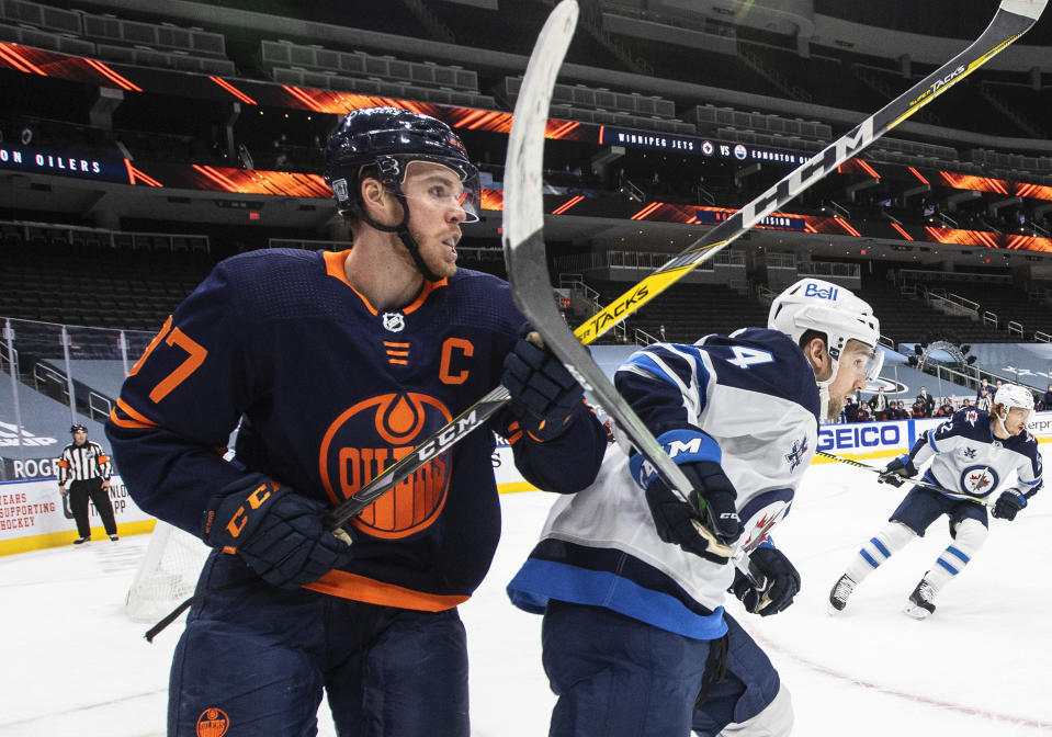Edmonton Oilers' Connor McDavid (97) and Winnipeg Jets' Neal Pionk (4) work in the corner during the second period of an NHL hockey game Wednesday, Feb. 17, 2021, in Edmonton, Alberta. (Jason Franson/The Canadian Press via AP)