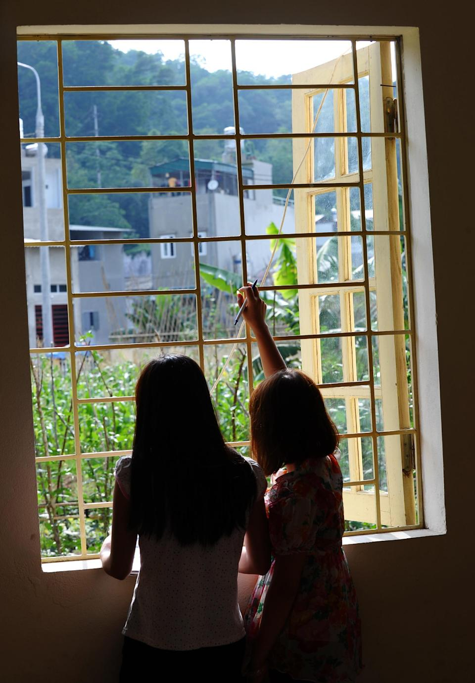 H'mong ethnic teenager May Na (L) (whose name has been changed to protect her identity) and a roommate look out from a window at a government-run centre for trafficked women in the northern city of Lao Cai, May 9, 2014 (AFP Photo/Hoang Dinh Nam)