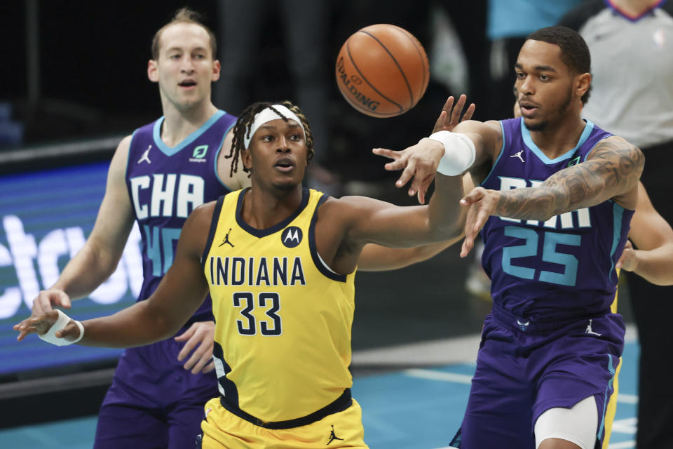 Charlotte Hornets forward P.J. Washington (25) passes the ball away from Indiana Pacers center Myles Turner (33) during the first half of an NBA basketball game in Charlotte, N.C., Wednesday, Jan. 27, 2021. (AP Photo/Nell Redmond)