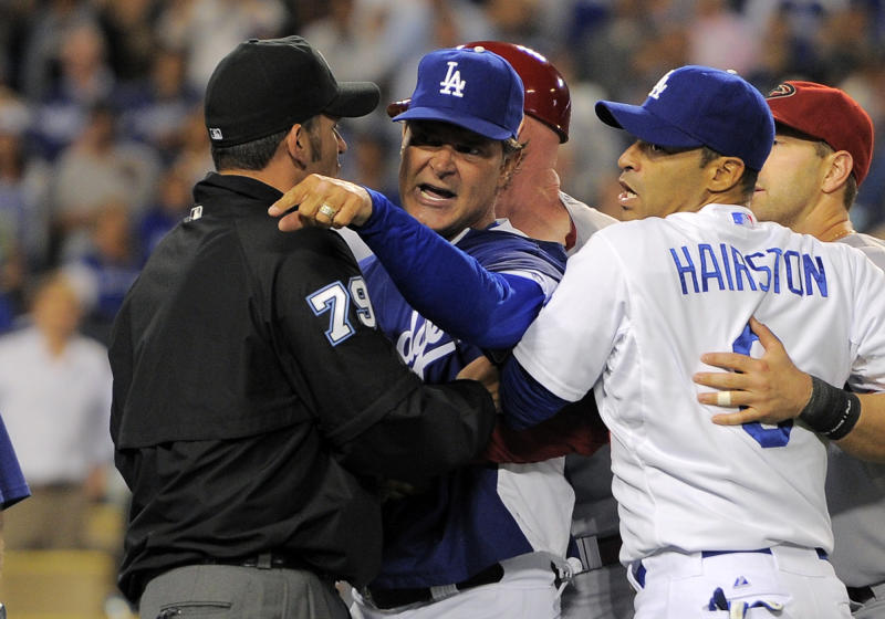 Los Angeles Dodgers manager Don Mattingly, center, yells at members of the Arizona Diamondbacks while umpire Manny Gonzalez holds him back as Jerry Hairston Jr. looks on after starting pitcher Zack Greinke was hit by a pitch during the seventh inning of their baseball game, Tuesday, June 11, 2013, in Los Angeles.  (AP Photo/Mark J. Terrill)
