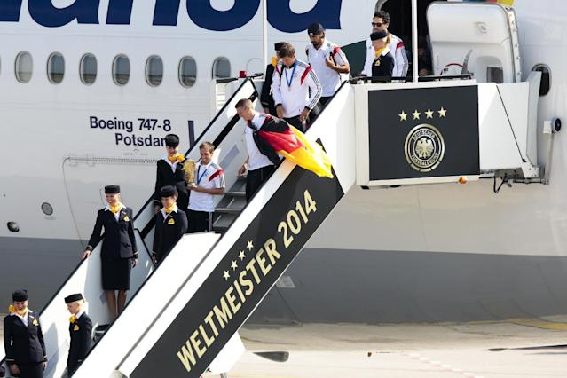 """The players of German national soccer team Philipp Lahm, Sebastian Schweinsteiger, Thomas Mueller, Sami Khedira and Mats Hummels from left, arrive at Tegel airport in Berlin Tuesday, July 15, 2014. G Germany's World Cup-winning team has returned home from Brazil to celebrate the country's fourth title with huge crowds of fans. The team's Boeing 747 touched down at Berlin's Tegel airport midmorning Tuesday after flying a lap of honor over the """"fan mile"""" in front of the landmark Brandenburg Gate. Words read World Champion 2014. (AP Photo/Markus Schreiber)"""