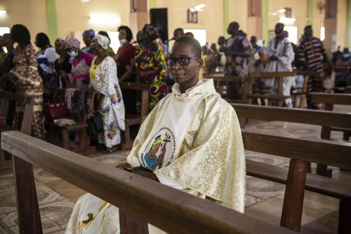 """Noel Henri Zongo, a priest at the Church of the Sangoulé Lamizana military camp in Ouagadougou, Burkina Faso, poses for a portrait Sunday, April 11, 2021. Just seven chaplains, hailing from Protestant, Catholic and Muslim faiths, are charged with spiritually advising some 11,000 soldiers and helping maintain their morale. The troops """"face death every day. ... At this moment they also need to have much more spiritual help,"""" he says. (AP Photo/Sophie Garcia)"""