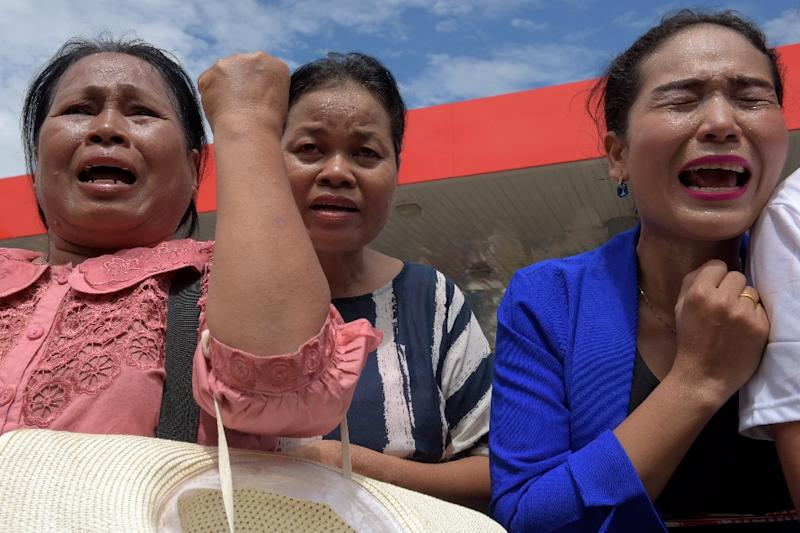 Women cry outside a convenience store where prominent political analyst Kem Ley was shot dead in Phnom Penh (AFP Photo/Tang Chhin Sothy)