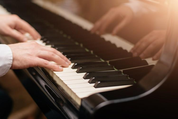 shutterstock_562181437 Close-up of a music performer's hand playing the piano, concert, art, music, sound, playing, hands, keyboard, classic, instrument, pianist