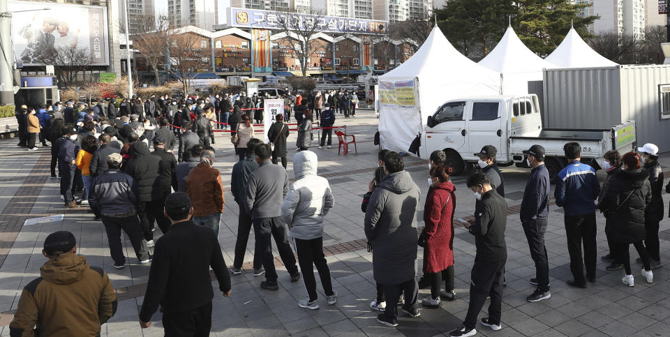 In this Tuesday, March 16, 2021 photo, migrant workers queue up to take coronavirus tests at a makeshift clinic in Seoul, South Korea. Britain's ambassador to South Korea on Thursday, March 18, criticised South Korean health authorities for mandating coronavirus tests on all foreign workers in capital Seoul and nearby Gyeonggi Province in a mass testing campaign that has triggered complaints about racial discrimination. (Lee Young-hwan/Newsis via AP)