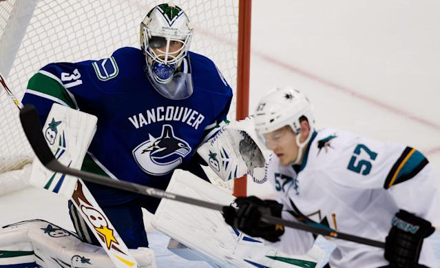 Vancouver Canucks' goalie Eddie Lack, left, follows the puck as San Jose Sharks' Tommy Wingels tries to get his stick on it during second period pre-season NHL hockey action in Vancouver, British Columbia on Monday Sept. 16, 2013. (AP Photo/The Canadian Press, Darryl Dyck)