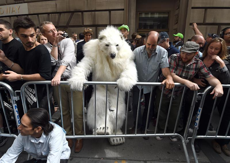 """A man dressed as a polar bear climbs a barricade as protestors take part in the """"Flood Wall Street"""" demonstrations on September 22, 2014 in New York (AFP Photo/Timothy A. Clary)"""