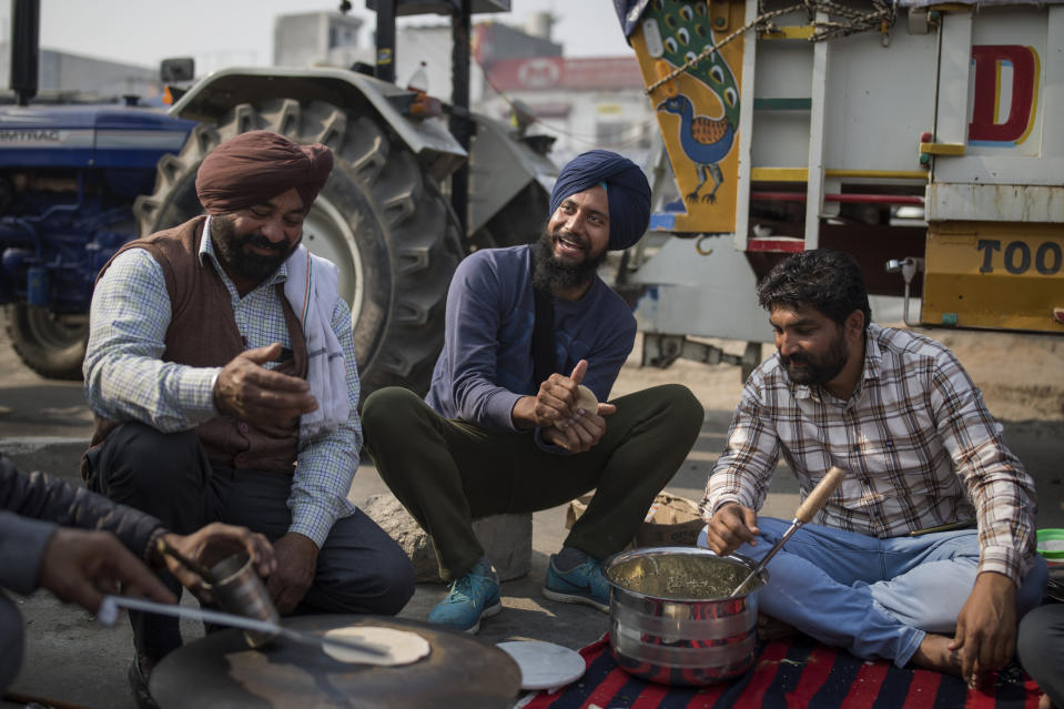 "Gurpreet Singh, 27, a Biotechnology student from a farming family, center, makes flat bread for breakfast as they block a major highway protesting against new farming laws, at the Delhi-Haryana state border, India, Tuesday, Dec. 1, 2020. ""India is in a recession. There are hardly any jobs and our country's secular fabric is in tatters,"" said Singh. ""At a time when India needs a healing touch, Modi is coming up with divisive, controversial laws. This is unacceptable and defies our constitutional values."" (AP Photo/Altaf Qadri)"