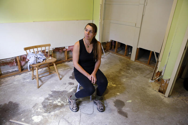 Jessica Klauzer-Zimmerman sits in her bedroom of her flood damaged home in Boulder, Colo., on Wednesday, Sept. 18, 2013. Klauzer-Zimmerman woke up Thursday Sept. 12, to knee-deep water inside her townhouse, and has since been dealing with a maze of phone calls with insurance agents. Each agent told her that her policy does not cover flood damage. Thousands of people who don't have flood insurance could face staggering costs to rebuild after the devastating floods in Colorado.(AP Photo/Ed Andrieski)