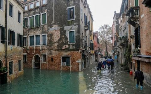 People walking outside during exceptionally high water levels in Venice - Credit: Reuters