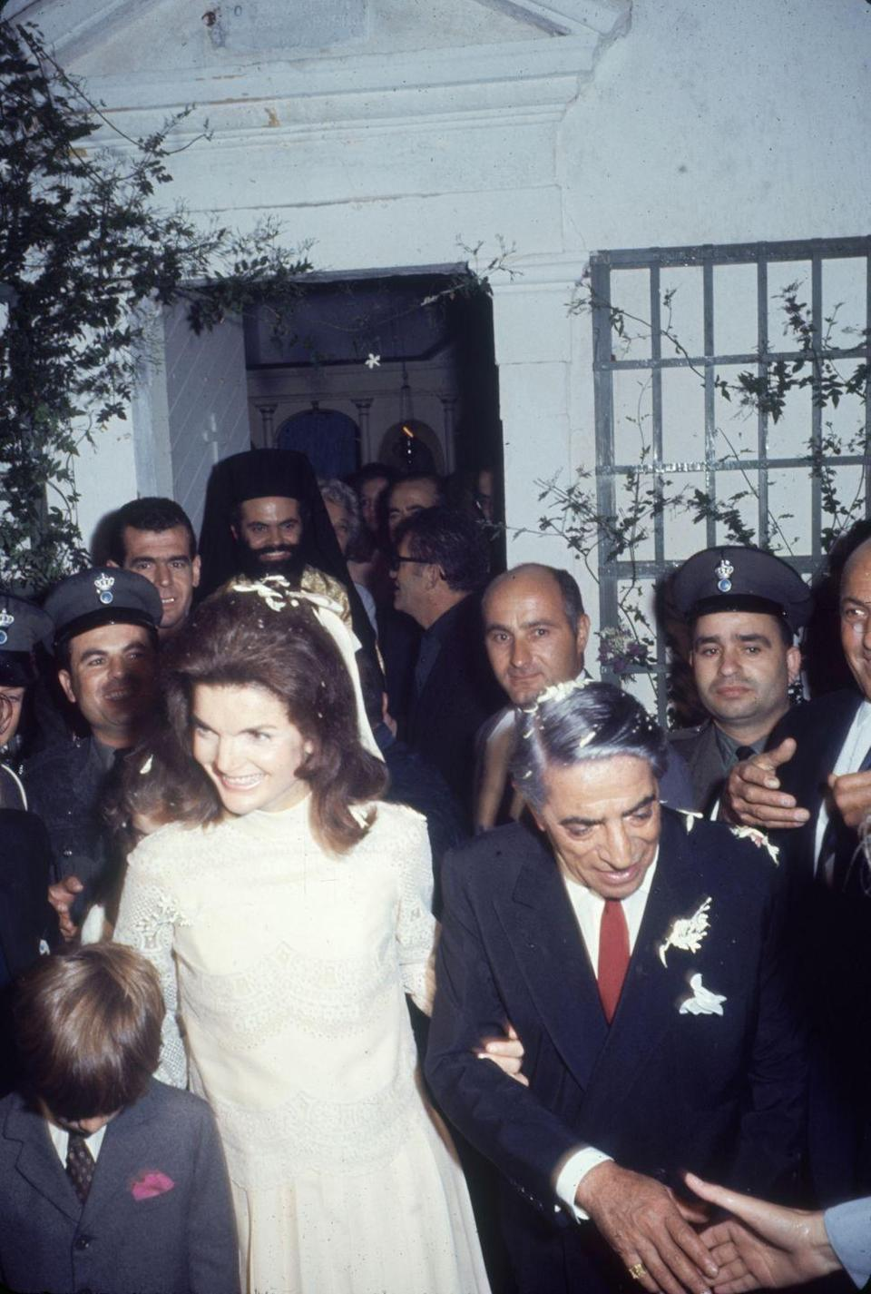 "<p>For her wedding to Greek magnate Aristotle Onassis, Jackie opted for a knee length pleated and lace <a href=""https://www.townandcountrymag.com/style/fashion-trends/g9947418/10-brands-jackie-kennedy-loved/?slide=9"" rel=""nofollow noopener"" target=""_blank"" data-ylk=""slk:Valentino dress"" class=""link rapid-noclick-resp"">Valentino dress</a> and a simple white hair bow. </p>"