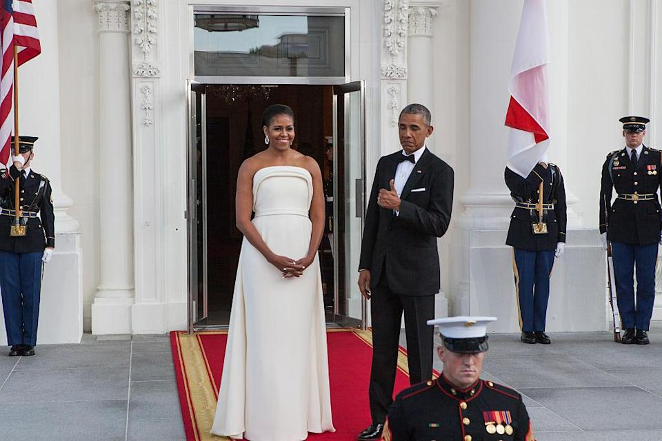 """<p>While welcoming the Singapore prime minister and his wife to the White House, the U.S. First Lady reached for a sculpted gown <a href=""""https://ca.style.yahoo.com/michelle-obama-and-lady-gaga-have-something-in-162402420.html"""" data-ylk=""""slk:by one of Lady Gaga's favourite designers;outcm:mb_qualified_link;_E:mb_qualified_link;ct:story;"""" class=""""link rapid-noclick-resp yahoo-link"""">by one of Lady Gaga's favourite designers</a>, Brandon Maxwell. It got a big thumbs up from President Obama, who looked dapper himself in a suit and bowtie. <i>(Photo by Cheriss May/NurPhoto via Getty Images)</i><br></p>"""