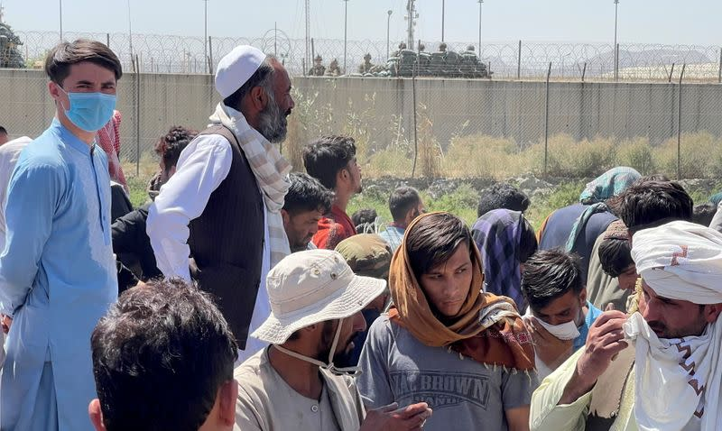 Crowds of people show their documents to U.S. troops outside the airport in Kabul