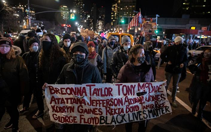 Protesters marching with a sign listing the names of black people killed by police - Jeenah Moon/Reuters