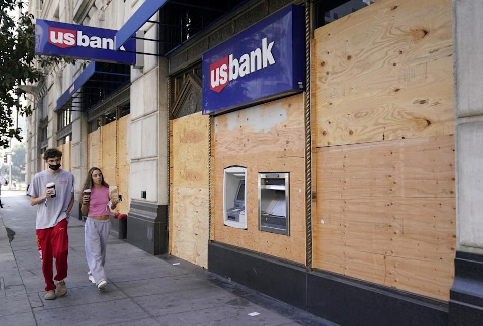 People walk past an ATM at a boarded-up U.S. Bank branch in downtown Los Angeles