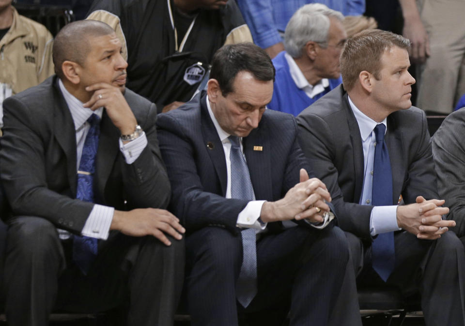 Duke coach Mike Krzyzewski, center, and assistant coaches Jeff Capel, left, and Steve Wojciechowski, right, watch the final minute of an NCAA college basketball game against Wake Forest in Winston-Salem, N.C., Wednesday, March 5, 2014. Wake Forest won 82-72. (AP Photo/Chuck Burton)