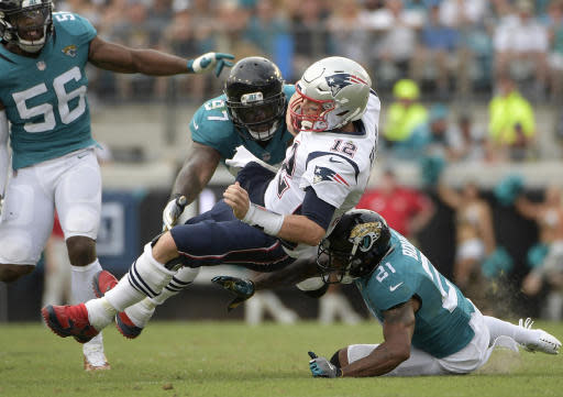 FILE - In this Sept. 16, 2018, file photo, New England Patriots quarterback Tom Brady (12) is tackled by Jacksonville Jaguars defensive tackle Malik Jackson (97) and defensive back A.J. Bouye (21) after scrambling for yardage during the second half of an NFL football game, in Jacksonville, Fla. The Jacksonville Jaguars, who ranked second in the NFL with 55 sacks in 2017, have four in two games _ on pace for 32 this season. Jacksonville hopes to end the trend against AFC South rival Tennessee on Sunday.(AP Photo/Phelan M. Ebenhack, File)
