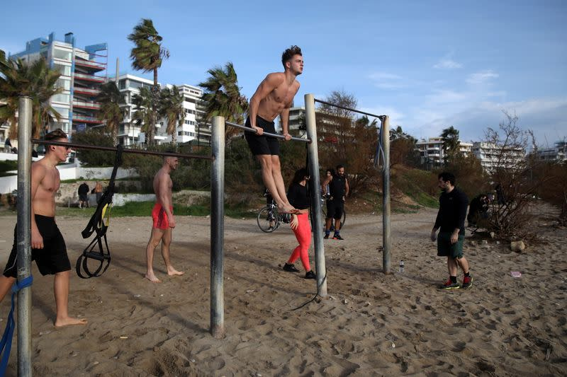 People exercise on a beach during an unusual warm day, amid the coronavirus disease (COVID-19) pandemic, in the southern suburb of Faliro in Athens