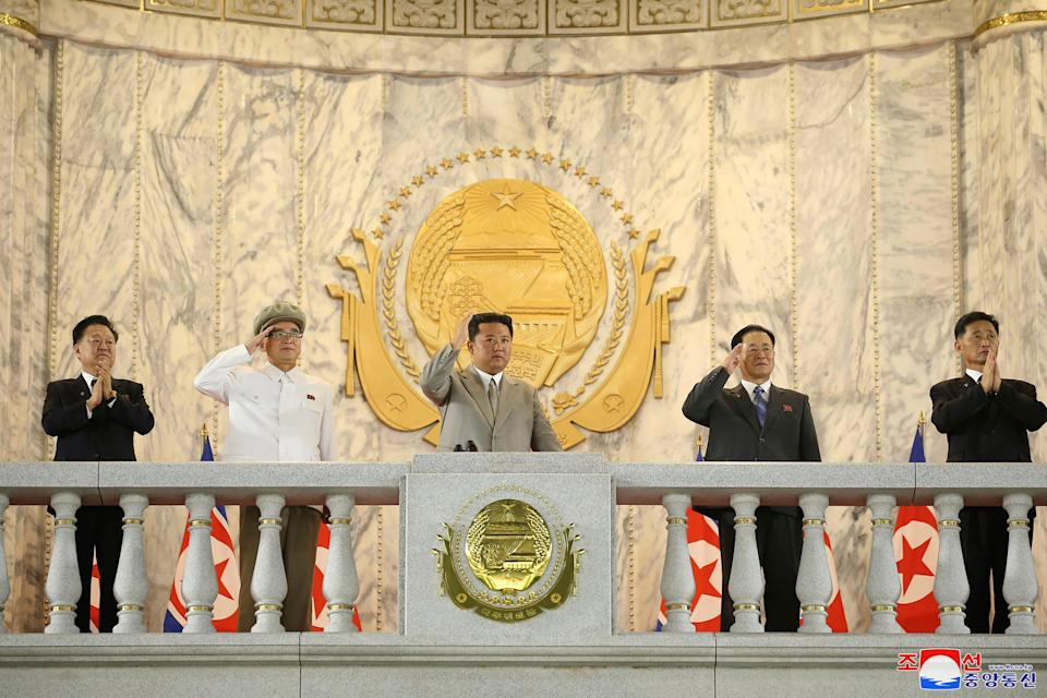 The North Korean leader Kim Jong Un, center, waves from a balcony toward the assembled troops and spectators.
