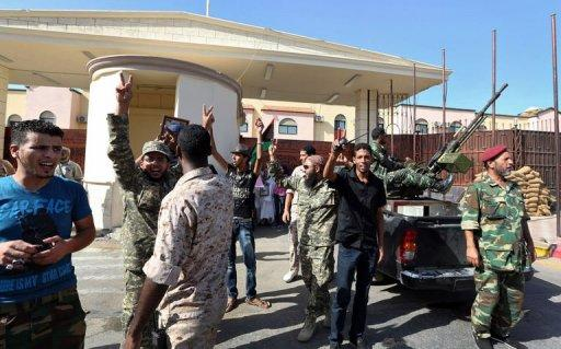 Libyan soldiers gather outside the Abu Salim prison in Tripoli to celebrate following extradition of Abdullah al-Senussi, fallen dictator Moamer Kadhafi's former spy chief, to Libya by Mauritania. Senussi could be held accountable for the Abu Salim prison 1996 massacre when more than 1,000 detainees were executed
