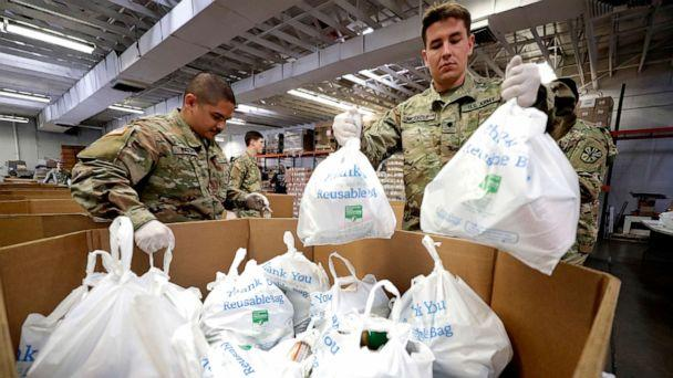 PHOTO: Arizona National Guard members pack and sort food items at a food bank, March 26, 2020, in Mesa, Ariz. (Matt York/AP)
