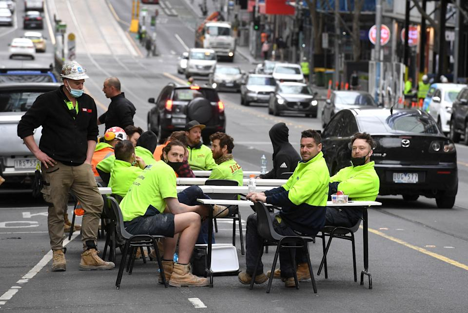 Construction workers take their lunch break on a busy street, disrupting traffic in Melbourne on September 17 to protest the closing of their onsite tea rooms by health officials. Source: Getty