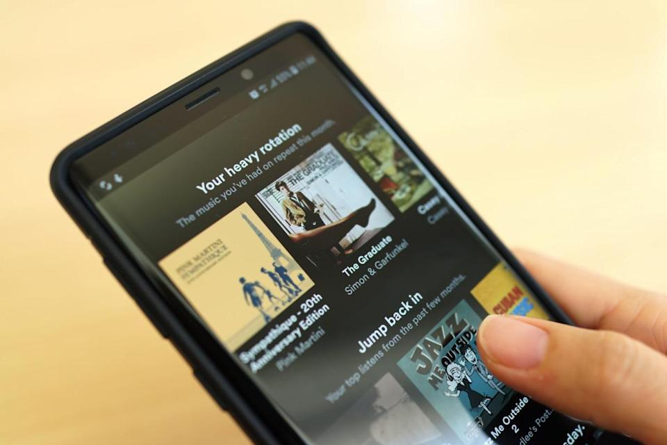 Close up woman holding Smartphone and using Spotify application on the screen