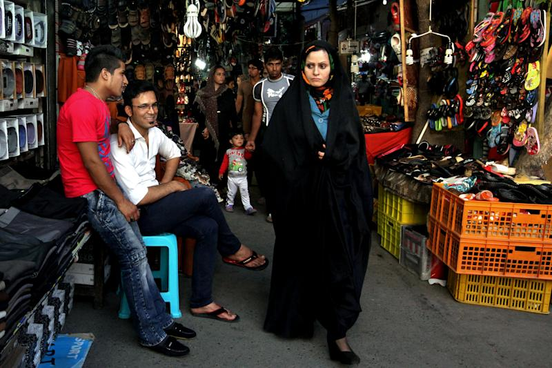 In this Tuesday, May 28, 2013 photo, an Iranian woman, makes her way, as two shopkeepers sit at left, at a bazaar, in downtown Tehran, Iran. On the roughneck streets in south Tehran, paramilitary volunteers look to the most hard-line presidential candidate as the best defender of the Islamic system. On the other end of Tehran's social ladder, a university professor plans to snub next week's election. In between is a mix of splintered views, apathy and indecision based on dozens of AP interviews suggesting a still wide open race. (AP Photo/Vahid Salemi)
