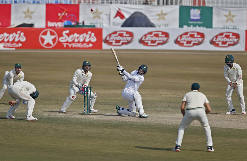 Pakistan's Nauman Ali, center, plays a shot for six while South Africa players watches during the fourth day of the second cricket test match between Pakistan and South Africa at the Pindi Stadium in Rawalpindi, Pakistan, Sunday, Feb. 7, 2021. (AP Photo/Anjum Naveed)