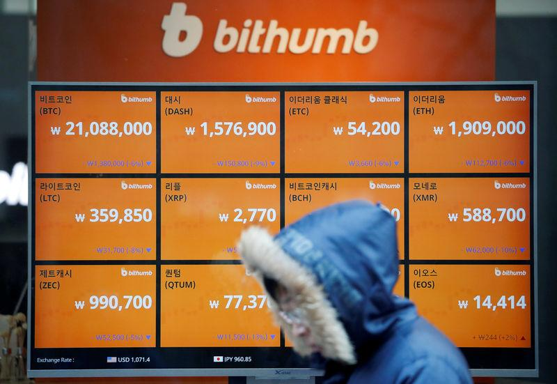 FILE PHOTO: A man walks past an electric board showing exchange rates of various cryptocurrencies at Bithumb cryptocurrencies exchange in Seoul