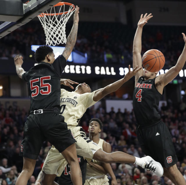 Wake Forest's Brandon Childress (0) is fouled as he drives between North Carolina State's Blake Harris (55) and Jericole Hellems (4) during the first half of an NCAA college basketball game in Winston-Salem, N.C., Tuesday, Jan. 15, 2019. (AP Photo/Chuck Burton)