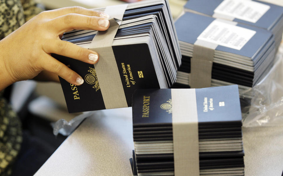 A worker gets more passport books as she works to reduce the passport backlog at the New Orleans Passport Agency in New Orleans. (AP Photo/Alex Brandon)