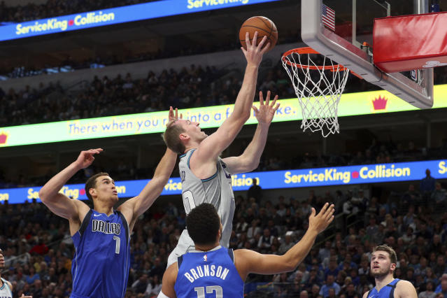 Dallas Mavericks forward Dwight Powell (7) and guard Jalen Brunson (13) try to defend against a shot by Charlotte Hornets forward Cody Zeller (40) in the first half in an NBA basketball game Saturday, Jan. 4, 2020, in Dallas. (AP Photo/Richard W. Rodriguez)
