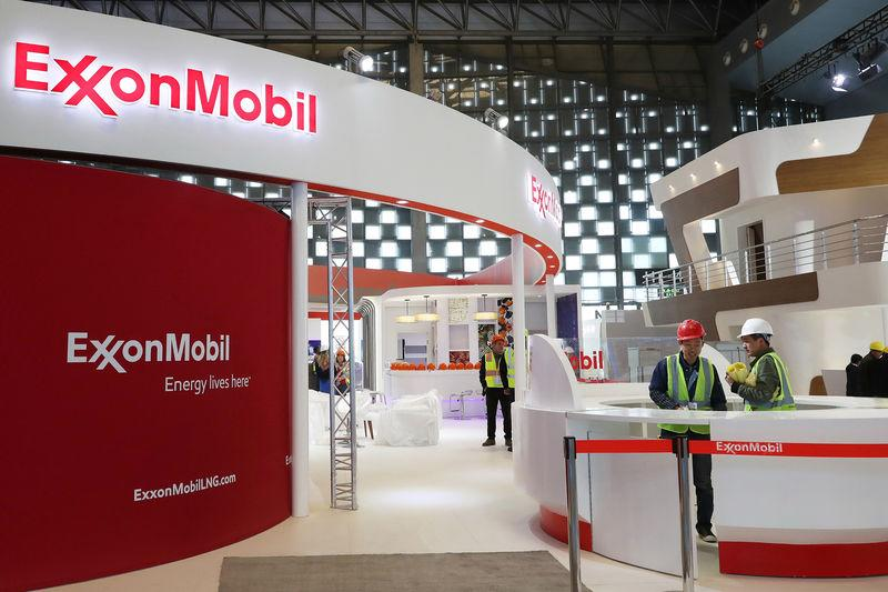 Workers are seen at the booth of ExxonMobil in preparation ahead of the LNG2019 in Shanghai