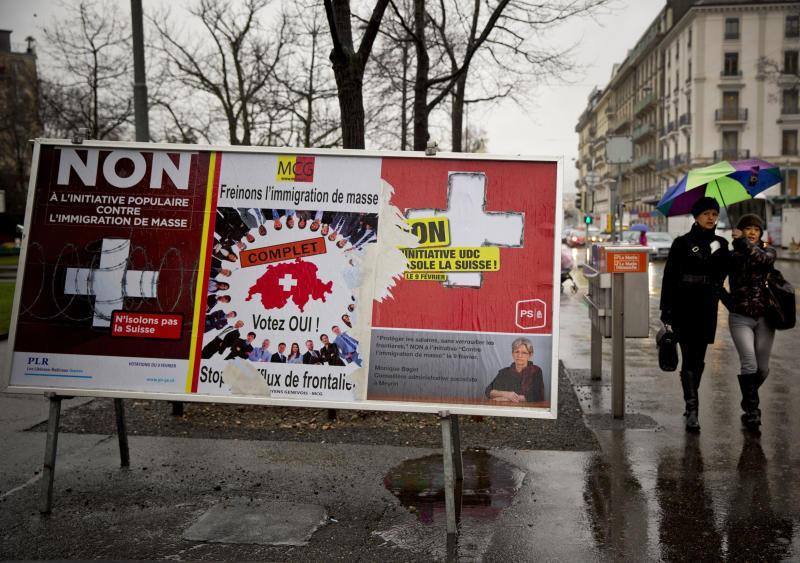 "Women pass by election placards , poster in center is for a stop of immigration, and posters at left and at right are for a yes to immigration, in Geneva, Switzerland, Monday, Feb. 10, 2014. The placard in the center reads ' stop the influence from the border'. The choice by Swiss voters to reimpose curbs on immigration is sending shock waves throughout the European Union, with EU leaders on Monday warning the Swiss had violated the ""sacred principle"" of Europeans' freedom of movement and politicians anxiously trying to gauge the vote's impact on burgeoning anti-foreigner movements in other countries. (AP Photo/Anja Niedringhaus)"
