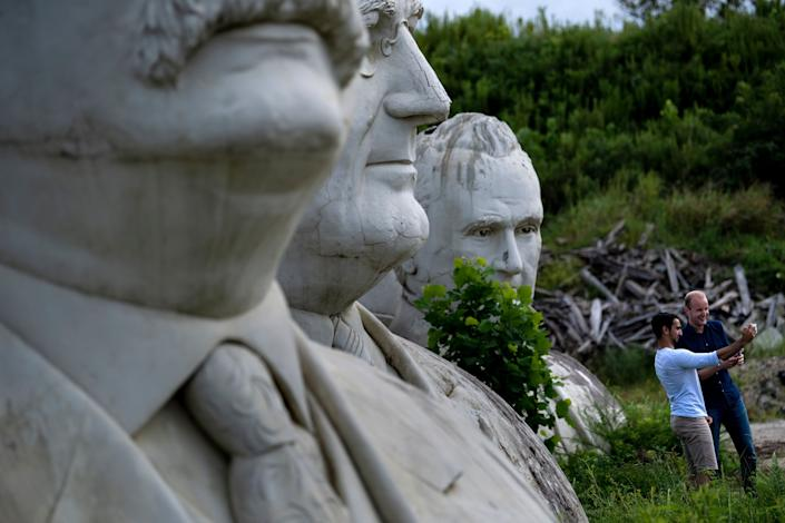 People pose for a selfie while touring the decaying remains of salvaged busts of former US Presidents on August 25, 2019, in Williamsburg, Virginia. (Photo: Brendan Smialowski/AFP/Getty Images)